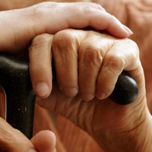 Adult helping senior in hospital, selective focus on hand